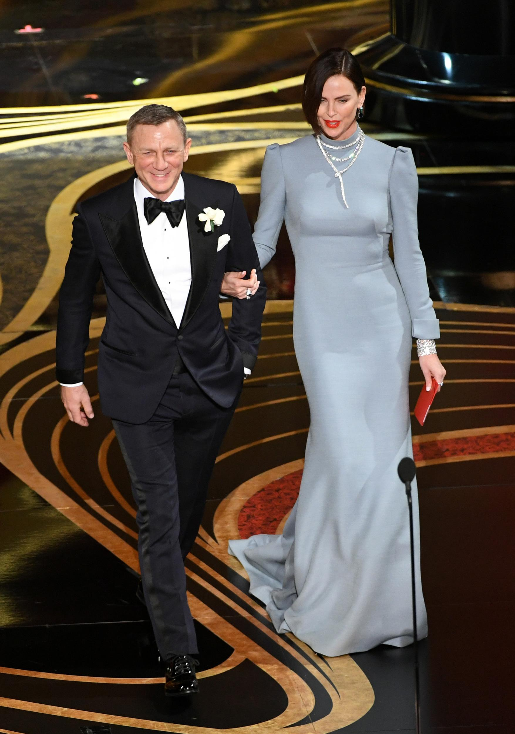 HOLLYWOOD, CALIFORNIA - FEBRUARY 24: (L-R) Daniel Craig and Charlize Theron walk onstage during the 91st Annual Academy Awards at Dolby Theatre on February 24, 2019 in Hollywood, California. (Photo by Kevin Winter/Getty Images)