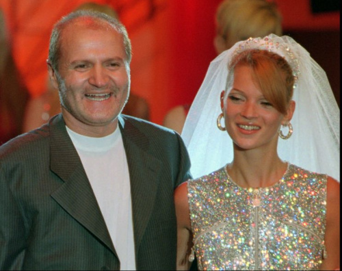 Italian fashion designer Gianni Versace, left, smiles with British model Kate Moss wearing a wedding gown after the presentation of his fall/winter 1995/96 haute couture collection, in Paris, France on Saturday July 8, 1995. Versace was recently indicted along with other Italian fashion designers for allegedly bribing Italian tax inspectors. (AP PHOTO/Lionel Cironneau)
