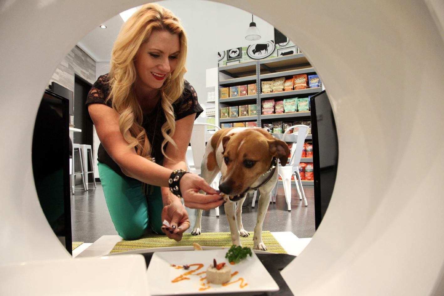 This Jan. 2, 2014, photo shows store co-owner, Janene Zakrajsek feeding a dog a gormet meal at the Pussy & Pooch Pet Lifestyle Center store in Beverly Hills, Calif. The Beverly Hills center, the newest of four locations, opened in December and markets itself as a lifestyle hub, complete with a holistic vet and wellness spa, animal trainer, grooming salon, bakery and meat market, training lab, social club, retail outlets and showroom. (AP Photo/Nick Ut)