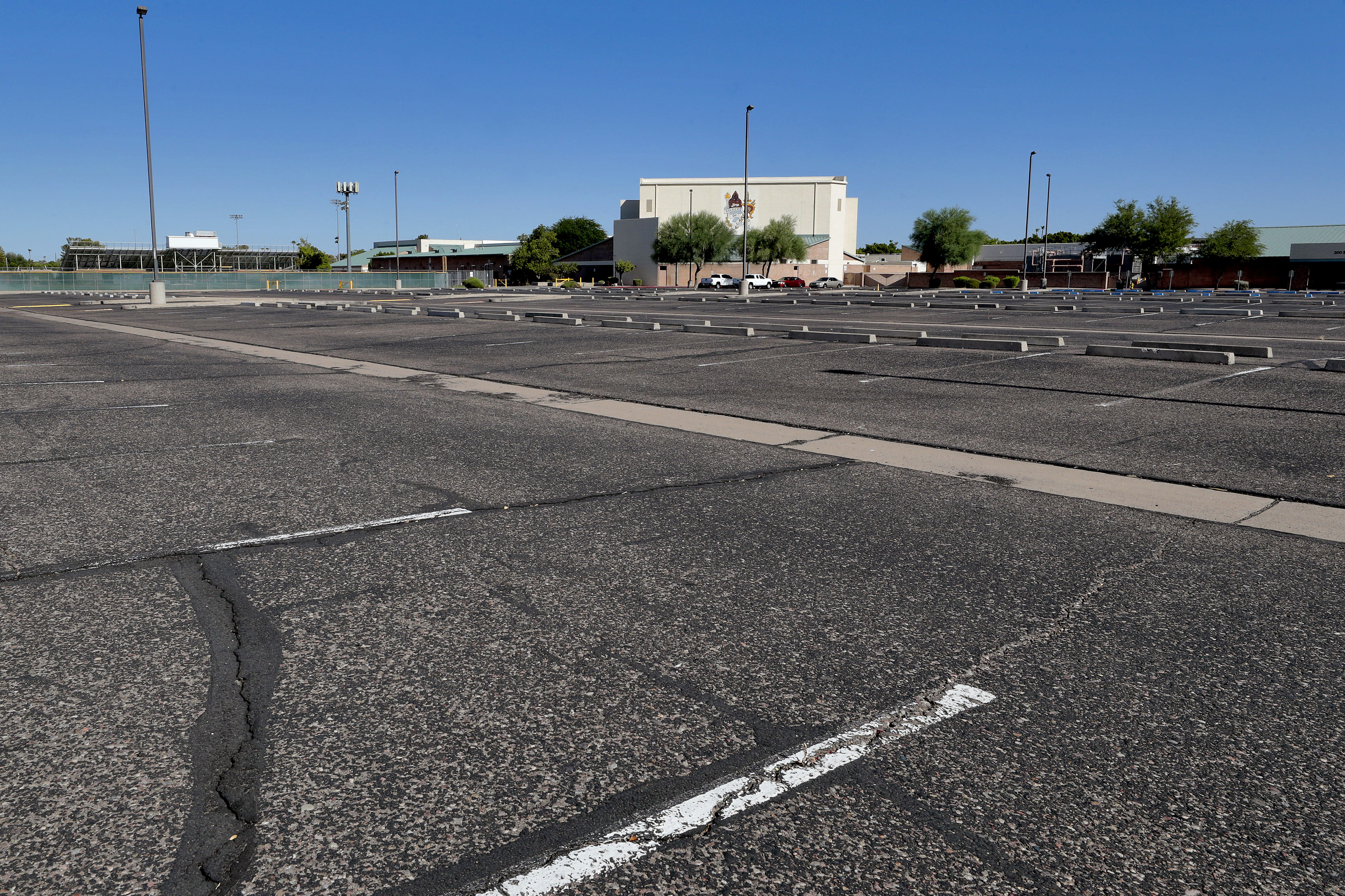 A parking lot is empty at a local high school Tuesday, June 30, 2020, in Tempe, Ariz. Schools will remain vacant two weeks longer this summer after Arizona Gov. Doug Ducey re-shut down bars, movie theaters, gyms, water parks and his delayed the start of school amid a dramatic resurgence of coronavirus cases. (AP Photo/Matt York)