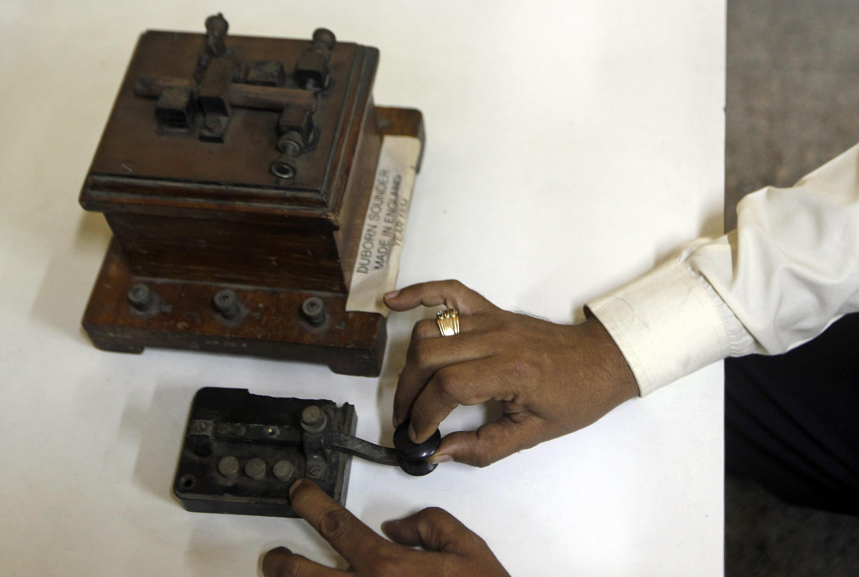 In this Friday, June 14, 2013 photo, a staff member of the central telegraph office shows an old telegraphic equipment which is no longer in use, in Mumbai, India. Just three decades ago - before reliable landlines were laid and well before the age of cheap cellphones arrived - the telegram was king across the vast Indian nation. On Monday, July 15, 2013, the state-run telecommunications company will send its final telegram, closing down a service that fast became a relic in an age of email, reliable land lines and ubiquitous cellphones. (AP Photo/Rajanish Kakade)