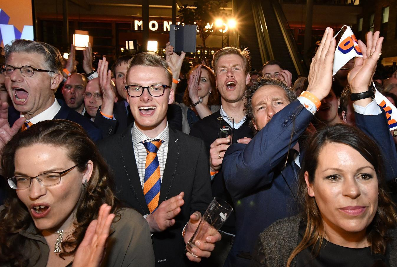 Supporters of Prime Minister Mark Rutte of the free-market VVD party cheer during Rutte's first appearance after exit poll results of the parliamentary elections were announced in The Hague, Netherlands, Wednesday, March 15, 2017. (AP Photo/Patrick Post)