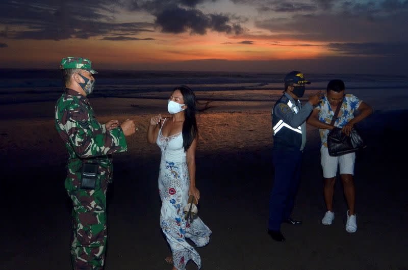 Officers wearing protective face masks give warning to visitors for wearing protective masks, amid the coronavirus disease (COVID-19) outbreak in Badung
