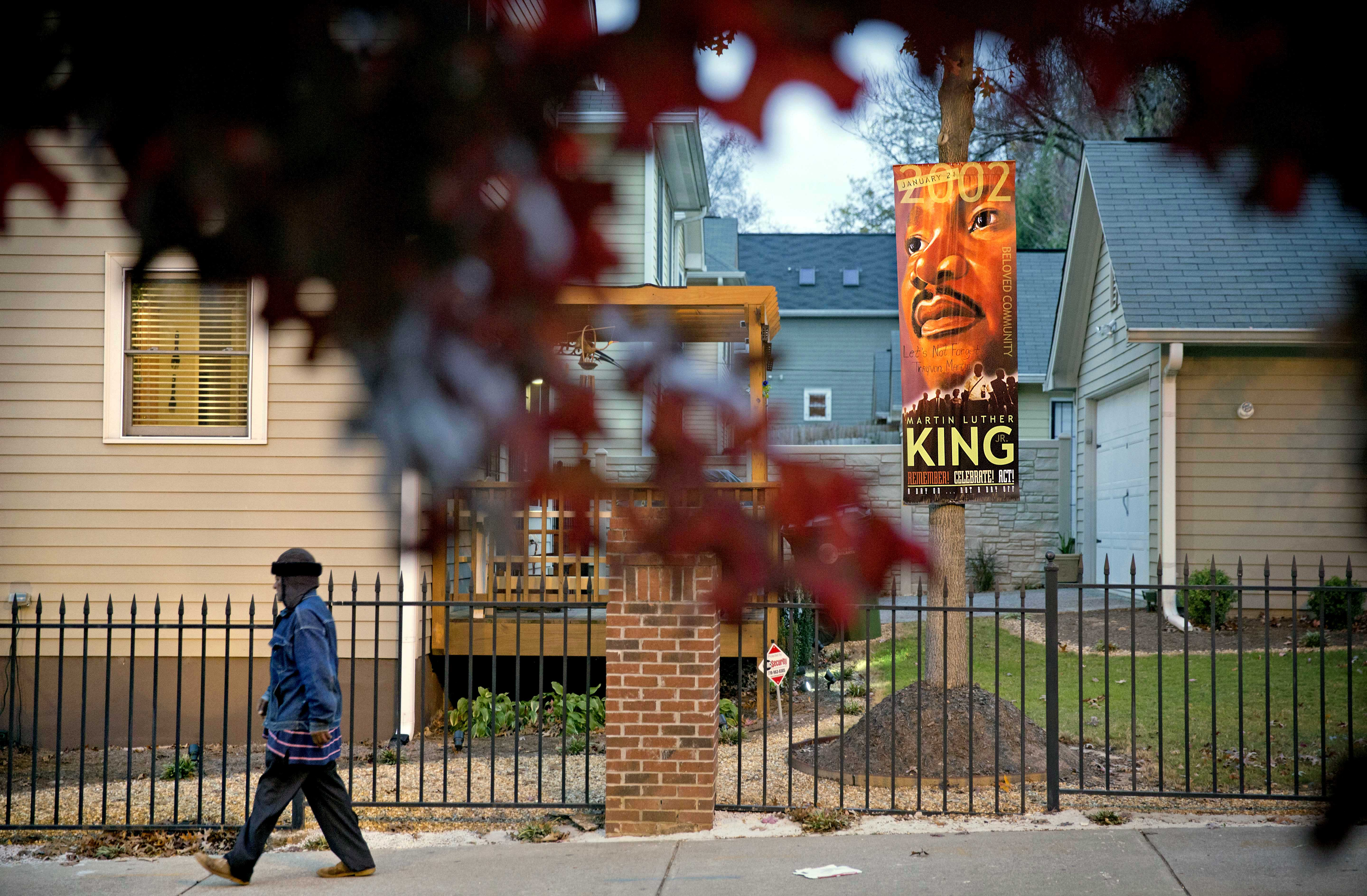 A man walks past a banner of civil rights leader Rev. Martin Luther King Jr., while walking through the Mechanicsville neighborhood surrounding the Atlanta Braves stadium, Wednesday, Nov. 20, 2013, in Atlanta. For the Braves, abandoning downtown Atlanta for the suburbs means moving closer to the team's fan base and developing money-making restaurants and amenities. Team officials say it's simply good business. But the decision also highlights long-standing disparities over wealth, where people live and even transportation, all facets of life connected to race and social class in Atlanta. The Braves will be moving from an area that's predominantly black and relatively poor compared to whiter Cobb County, where the team says more ticket-buyers live. Although it is long past segregation, the hometown of slain civil rights leader Martin Luther King is far from integrated, and the city's politics, business and even sports teams reflect that gap. (AP Photo/David Goldman)