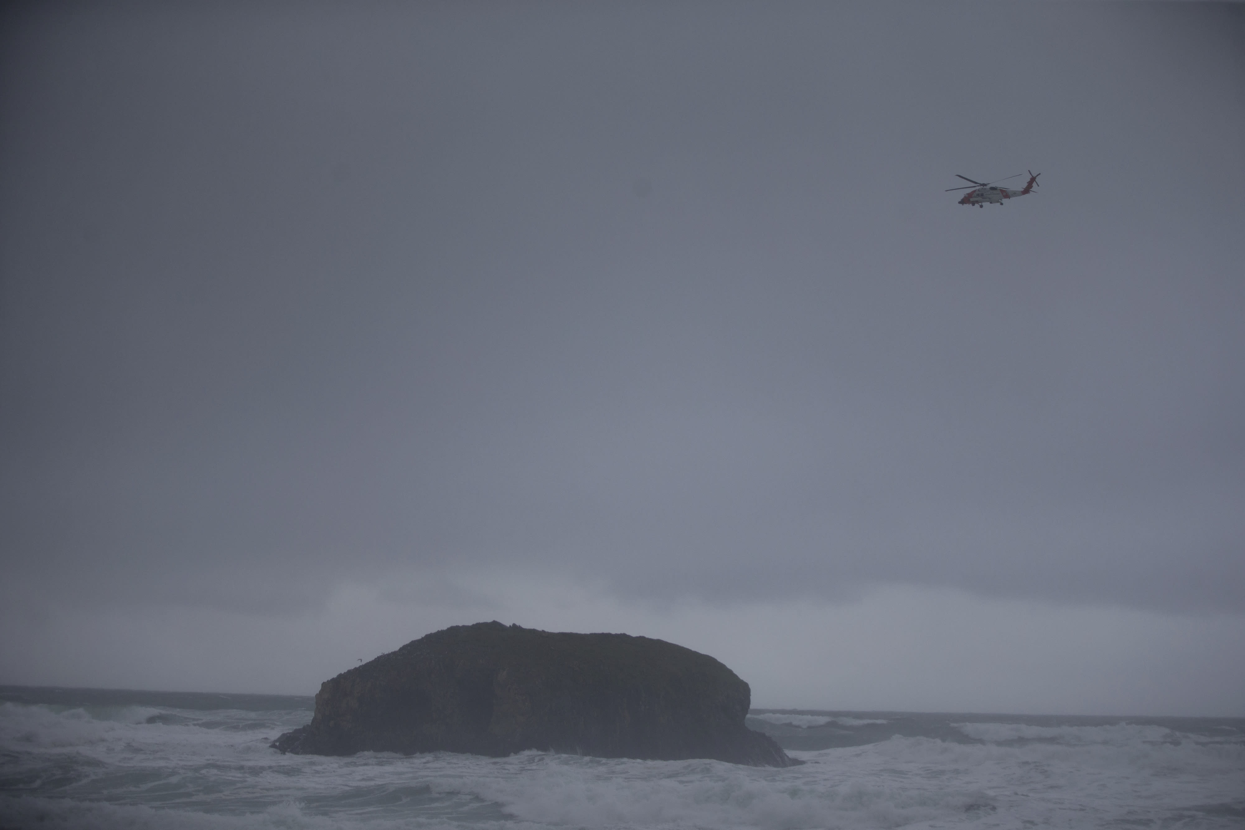 In this Sunday, Jan. 12, 2020 photo, a Coast Guard helicopter continues to search for a missing boy near Falcon Cove Beach in Clastop county, Ore. A 7-year-old girl is dead and her 4-year-old brother is missing after they and their father were swept into the ocean on the Oregon coast amid a high-surf warning. The father was holding the two children when a wave swept all three into the water Saturday, Jan. 11 in the Falcon Cove area, near the small coastal community of Cannon Beach, authorities said. (Mark Graves/The Oregonian via AP)