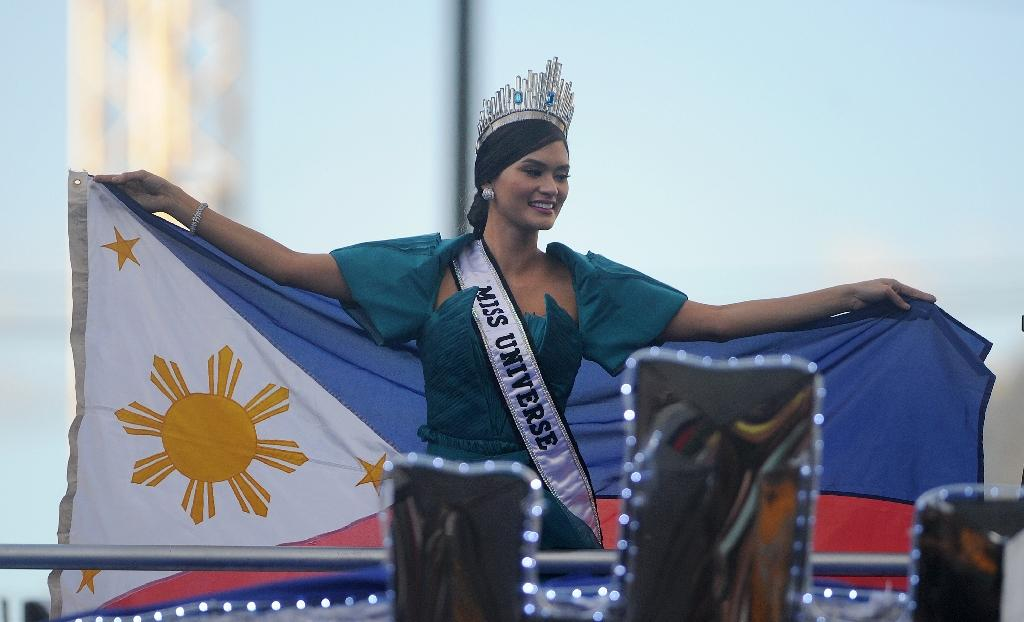 Miss Universe Pia Alonzo Wurtzbach waves a Philippine flag during her victory homecoming parade in Manila on January 25, 2016 (AFP Photo/Noel Celis)