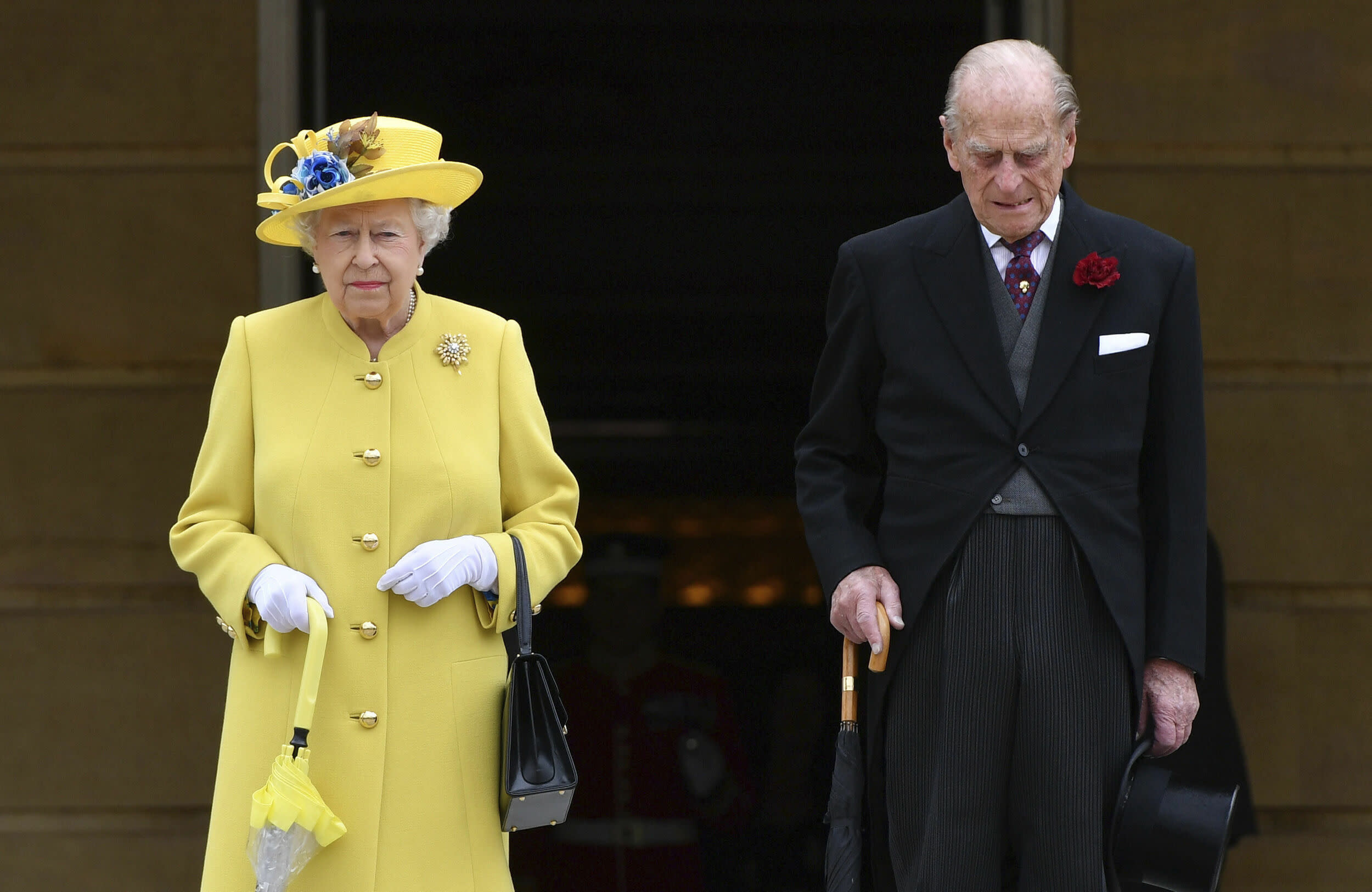 Britain's Queen Elizabeth and Prince Philip observe a minute's silence, at the start of a garden party at Buckingham Palace in London, Tuesday, May 23, 2017. The Islamic State group claimed responsibility Tuesday for the suicide attack at an Ariana Grande show that left over 20 people dead and dozens injured. (Dominic Lipinski/Pool Photo via AP)