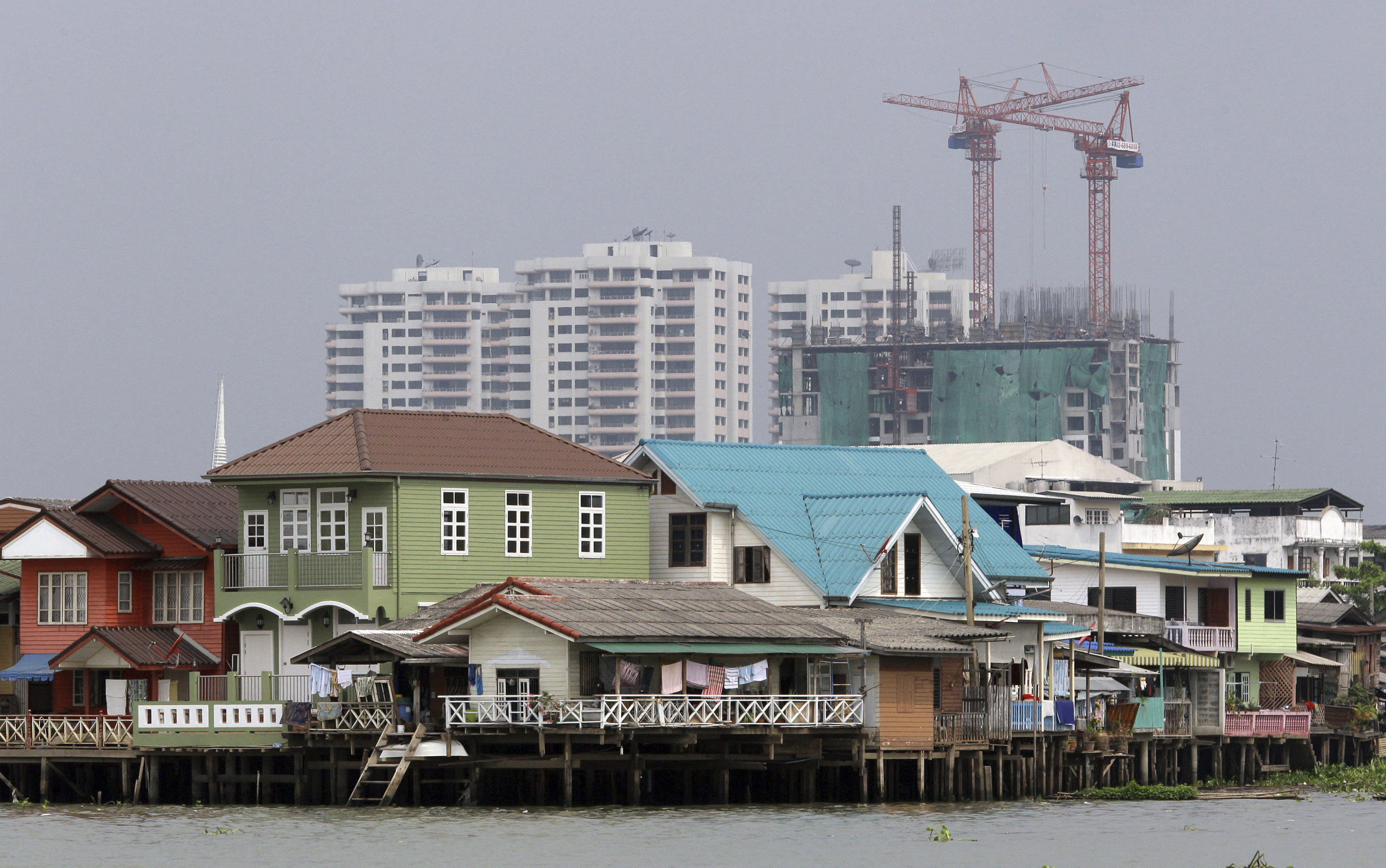 FILE - In this March 26, 2012 file photo, residences on stilts sit along the Chao Phraya River with a construction site in the background in Bangkok, Thailand. Sea level rise projections show Bangkok could be at risk of inundation in 100 years unless preventive measures are taken. (AP Photo/Sakchai Lalit, File)