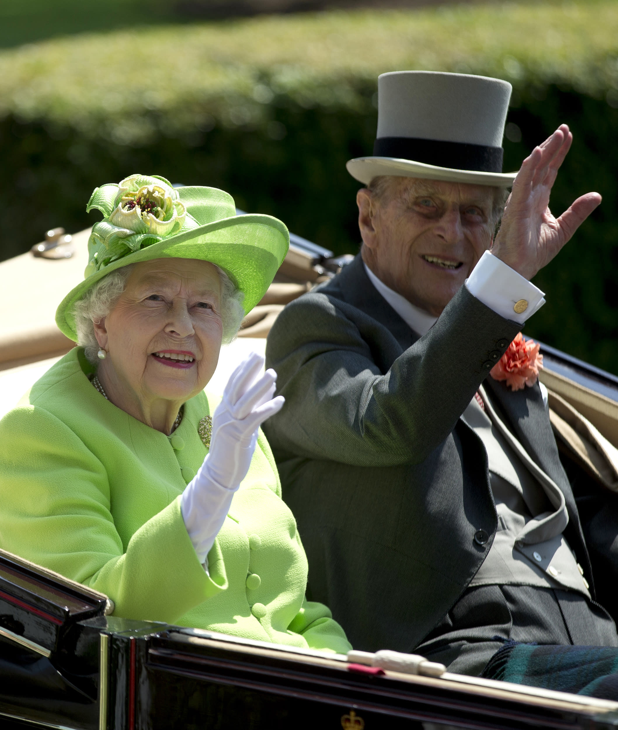 Britain's Queen Elizabeth II, waves to the crowd with Prince Philip at right, as they arrive by open carriage to the parade ring on the first day of the Royal Ascot horse race meeting in Ascot, England, Tuesday, June 20, 2017. (AP Photo/Alastair Grant)