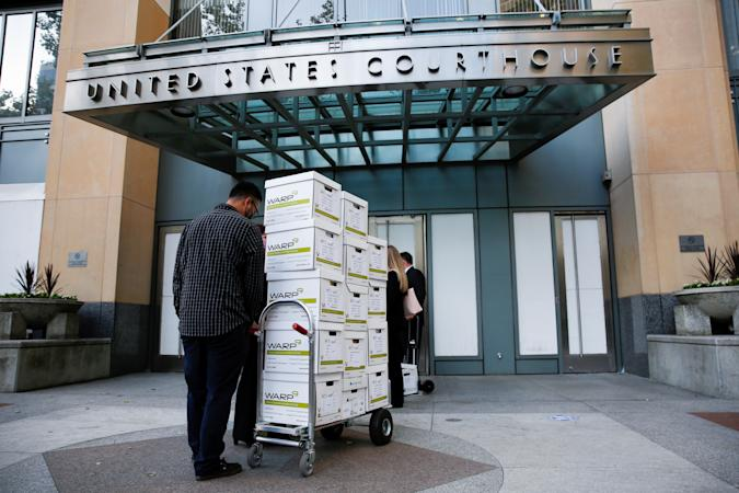 Court documents provided by Gibson, Dunn and Crutcher, LLP, the law firm representing Apple, are brought to the Oakland Federal courthouse for a weeks-long antitrust trial at federal court in Oakland, California, U.S., May 3, 2021.  REUTERS/Brittany Hosea-Small