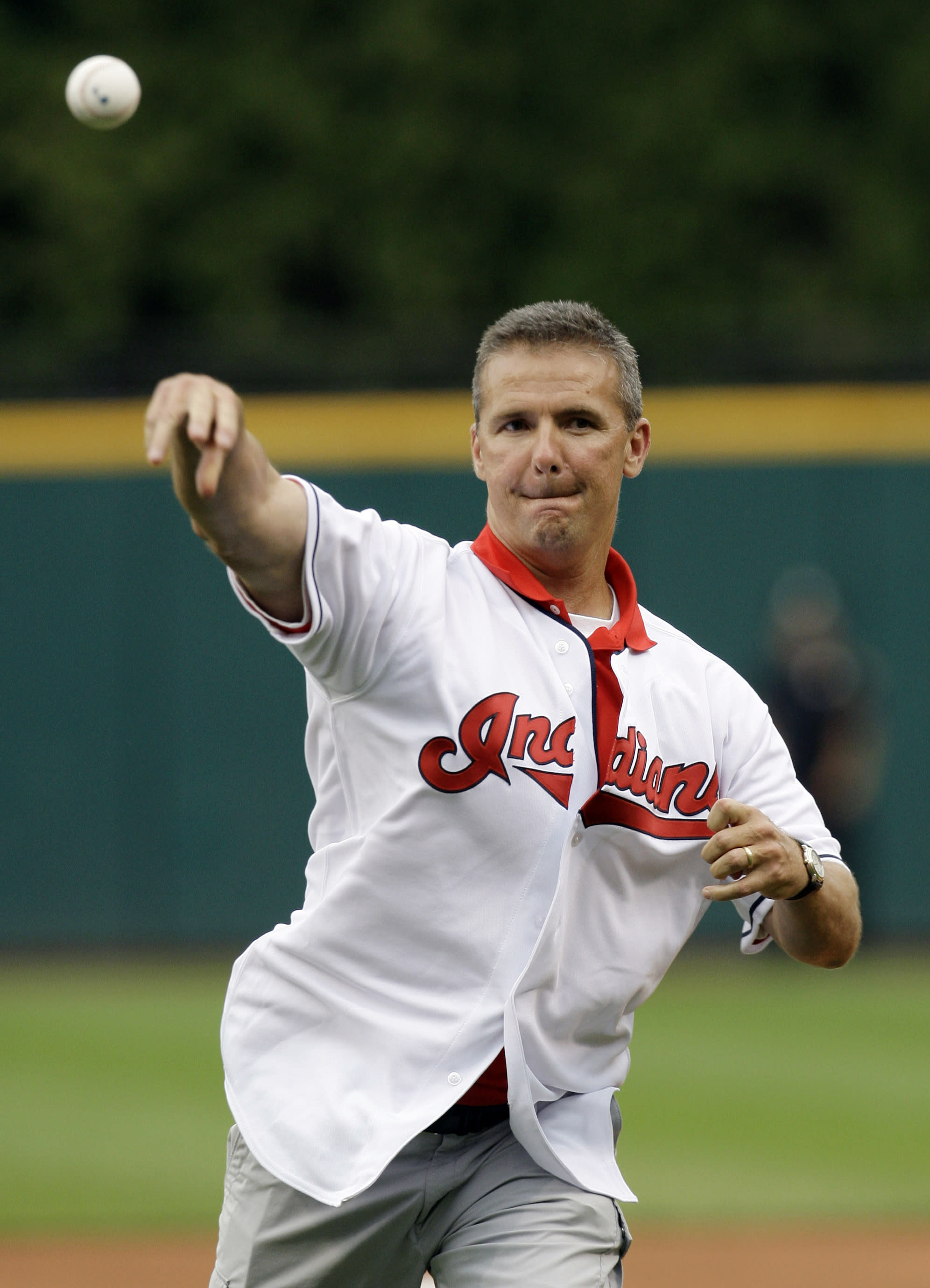 Ohio State football coach Urban Meyer throws out the ceremonial first pitch before the Cleveland Indians play the Cincinnati Reds in a baseball game, Monday, June 18, 2012, in Cleveland. (AP Photo/Tony Dejak)