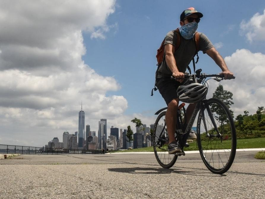A person rides a bike on Governors Island in New York City. Governors Island reopens to visitors on Wednesday with limited capacity due to continued concerns about the coronavirus.