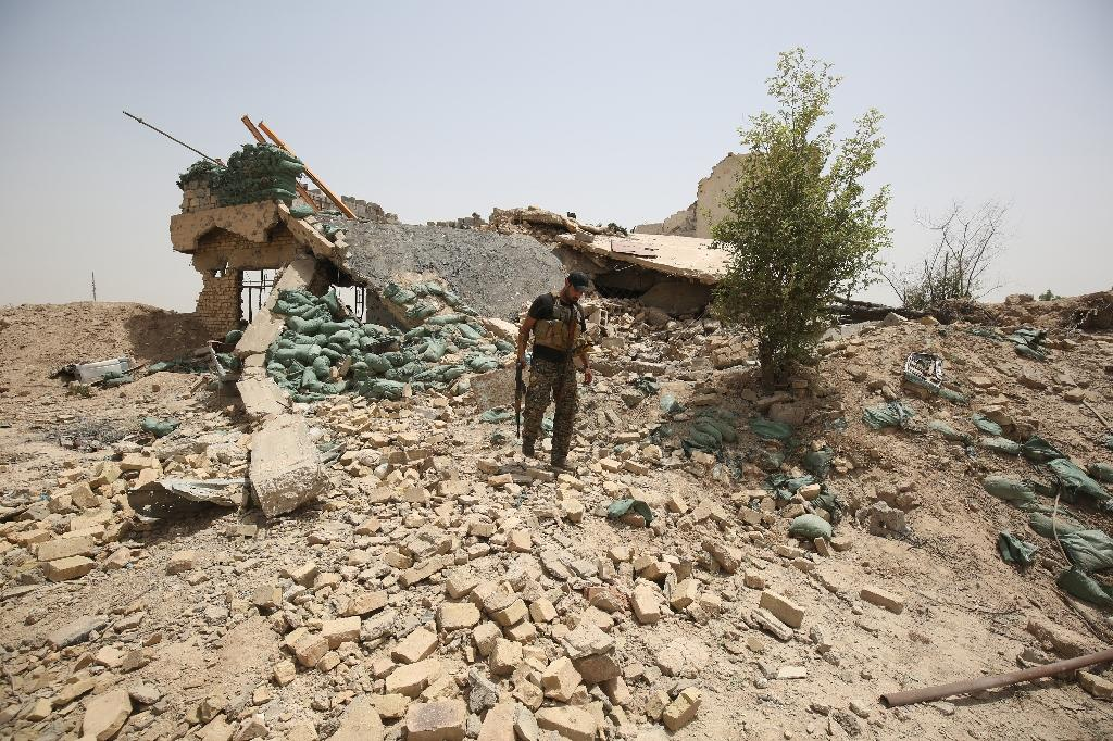 A member of the Iraqi government forces walks amid the rubble of a destroyed building on the front line near the village of al-Azraqiyah, northwest of the city of Fallujah, on June 5, 2016 (AFP Photo/Ahmad al-Rubaye)