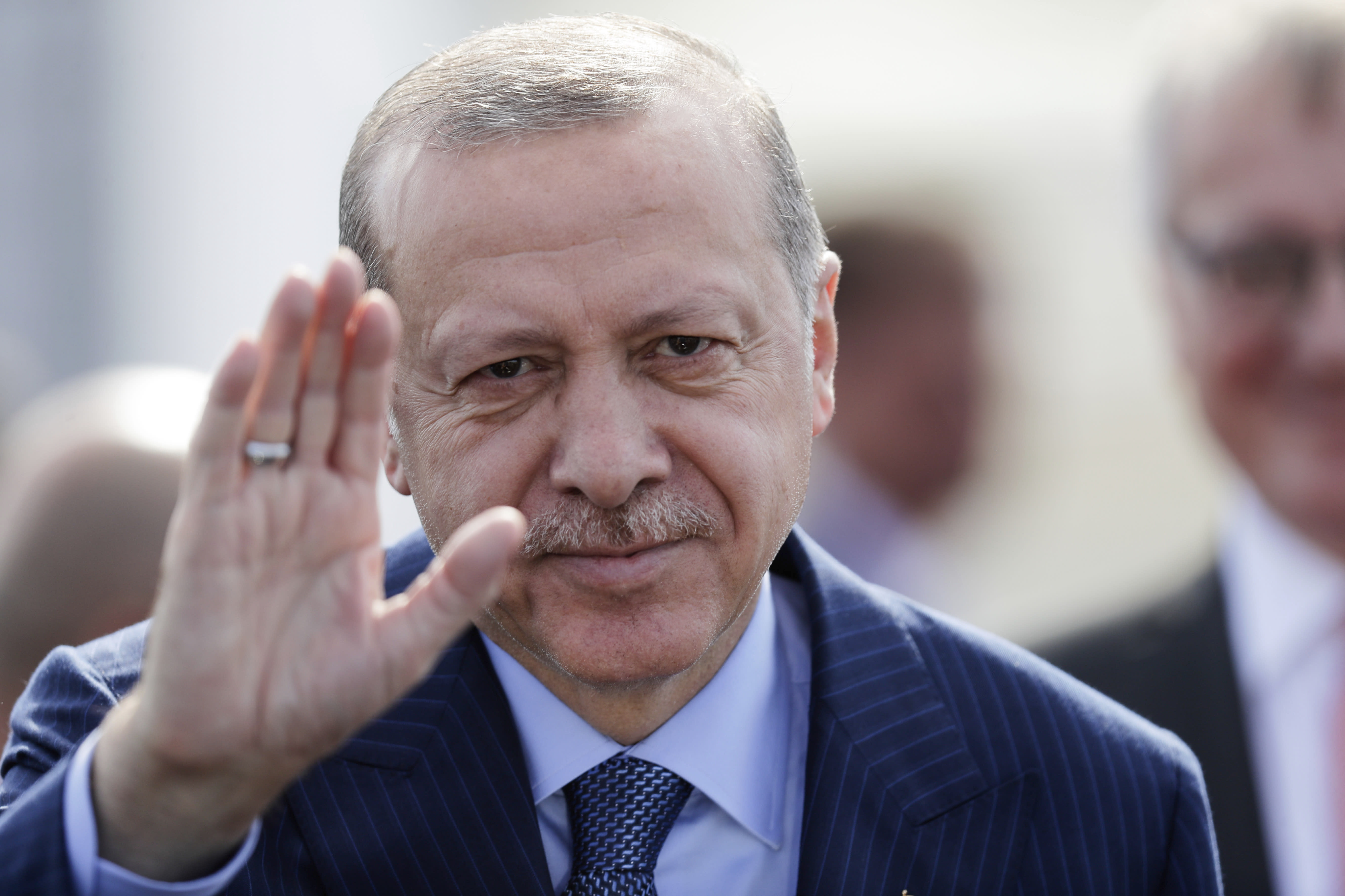 Turkey's President Recep Tayyip Erdogan waves to media after arrives at the airport Tegel for an official state visit in Germany at the capital Berlin, Thursday, Sept. 27, 2018. (AP Photo/Markus Schreiber)