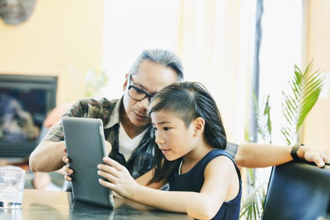 Daughter and father working on digital tablet while doing homework at dining room table