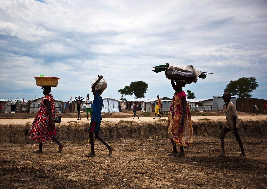 People walk through the UN base outside Bentiu, South Sudan, on September 17, 2015