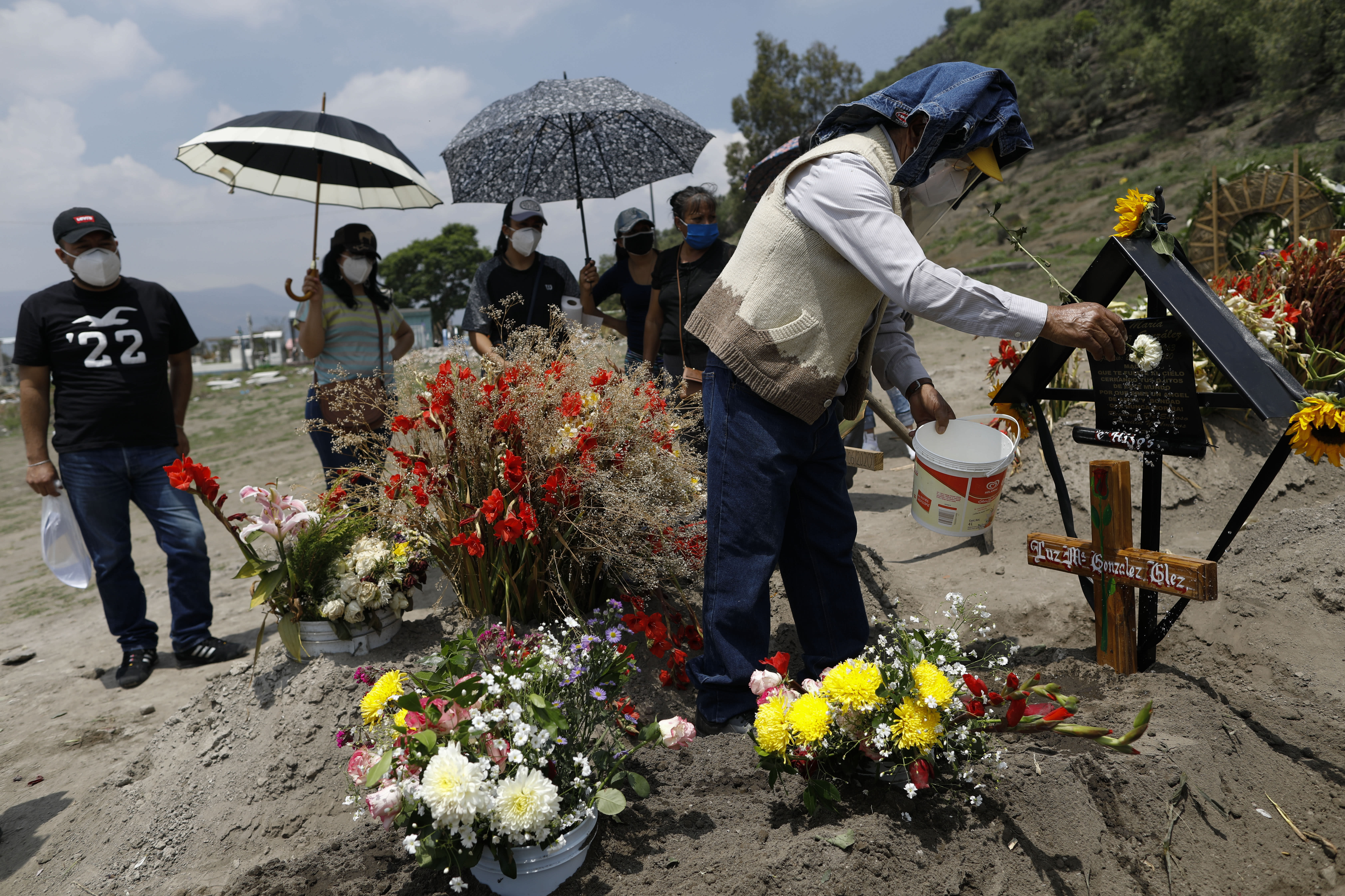 David Gonzalez uses a flower to sprinkle holy water onto the grave of his wife, Luz Maria Gonzalez, as they mark the 9th day since her burial in the Municipal Cemetery of Valle de Chalco on the outskirts of Mexico City, Saturday, July 4, 2020. Gonzalez, 56, who had long suffered from asthma, diabetes, and hypertension, died two days after her 29-year-old son, who was hospitalized for breathing problems and a cough before dying of complications said to be related to pneumonia and undiagnosed diabetes. (AP Photo/Rebecca Blackwell)