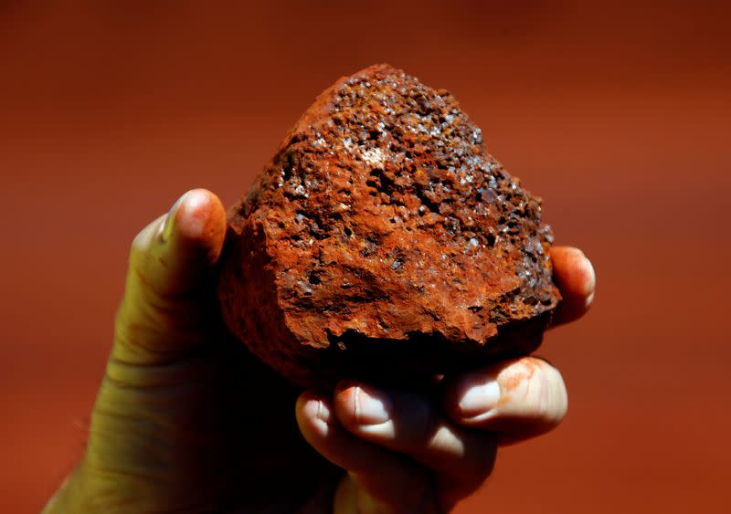 FILE PHOTO: A miner holds a lump of iron ore at a mine located in the Pilbara region of Western Australia