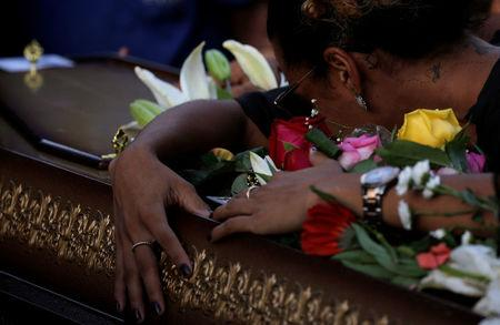 A relative reacts over the coffin of Rio de Janeiro's city councillor Marielle Franco, 38, who was shot dead, during her burial in Rio de Janeiro, Brazil March 15, 2018. REUTERS/Ricardo Moraes