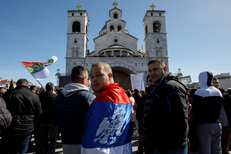 A man wrapped in a Serbian flag reacts before a protest march against a new law on religious freedom and legal rights of religious organizations in Podgorica