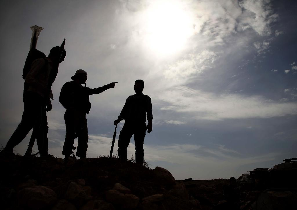 Syrian rebel-fighters with the National Liberation Front (NLF) stand on a hill overlooking regime-held areas in the northwestern countryside of Aleppo province on October 9, 2018 (AFP Photo/Aaref WATAD)