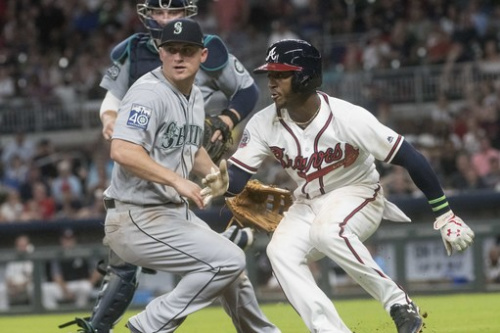Atlanta Braves' Ozzie Albies, right, hits the brakes in a rundown as Seattle Mariners try to get him out. (AP)