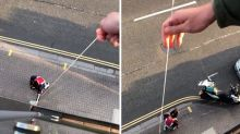 Couple collect food order by lowering bag from their balcony