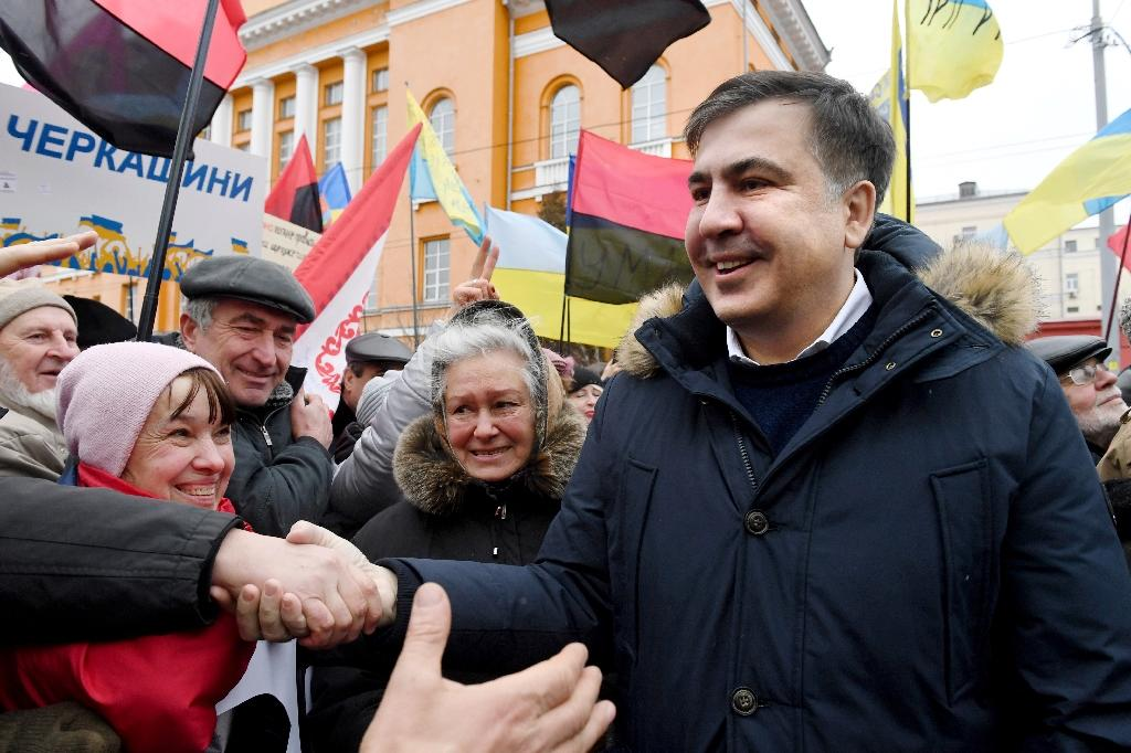 Former Georgian president Mikheil Saakashvili (R), one of the leader of the Ukrainian opposition, shakes hands with supporters and activists during a march calling for the President Petro Poroshenko impeachment, in Kiev, on February 4, 2018