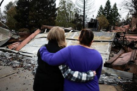 Irma Corona (R) comforts neighbor Gerryann Wulbern in front of the remains of Wulbern's home after the two returned for the first time since the Camp Fire in Paradise, California, U.S. November 22, 2018. REUTERS/Elijah Nouvelage