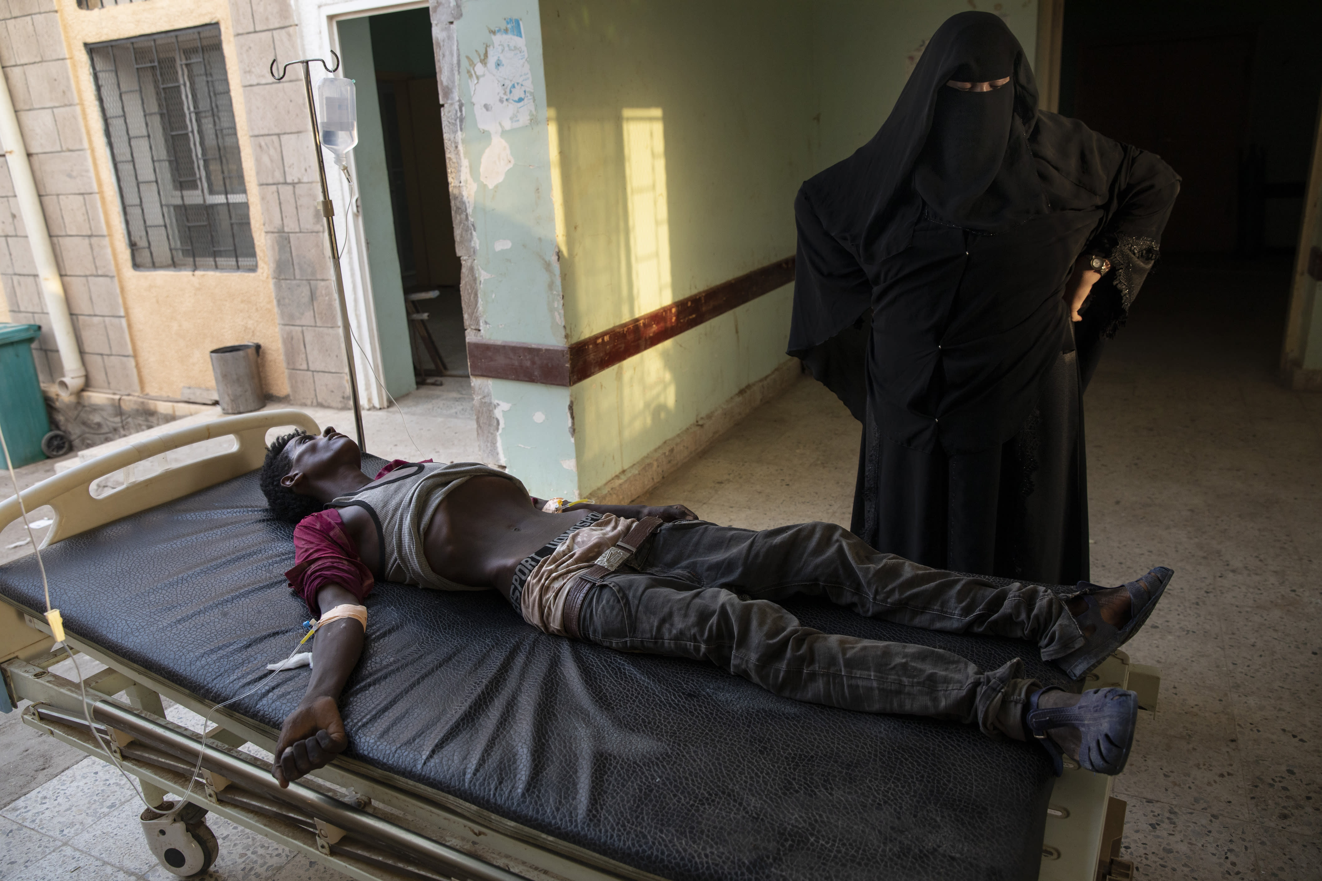 In this Aug. 1, 2019 photo, an Ethiopian Tigray migrant who was imprisoned by traffickers for months, lies on a gurney accompanied by a nurse at the Ras al-Ara Hospital in Lahj, Yemen. Nurses gave him fluids but he died several hours later. (AP Photo/Nariman El-Mofty)
