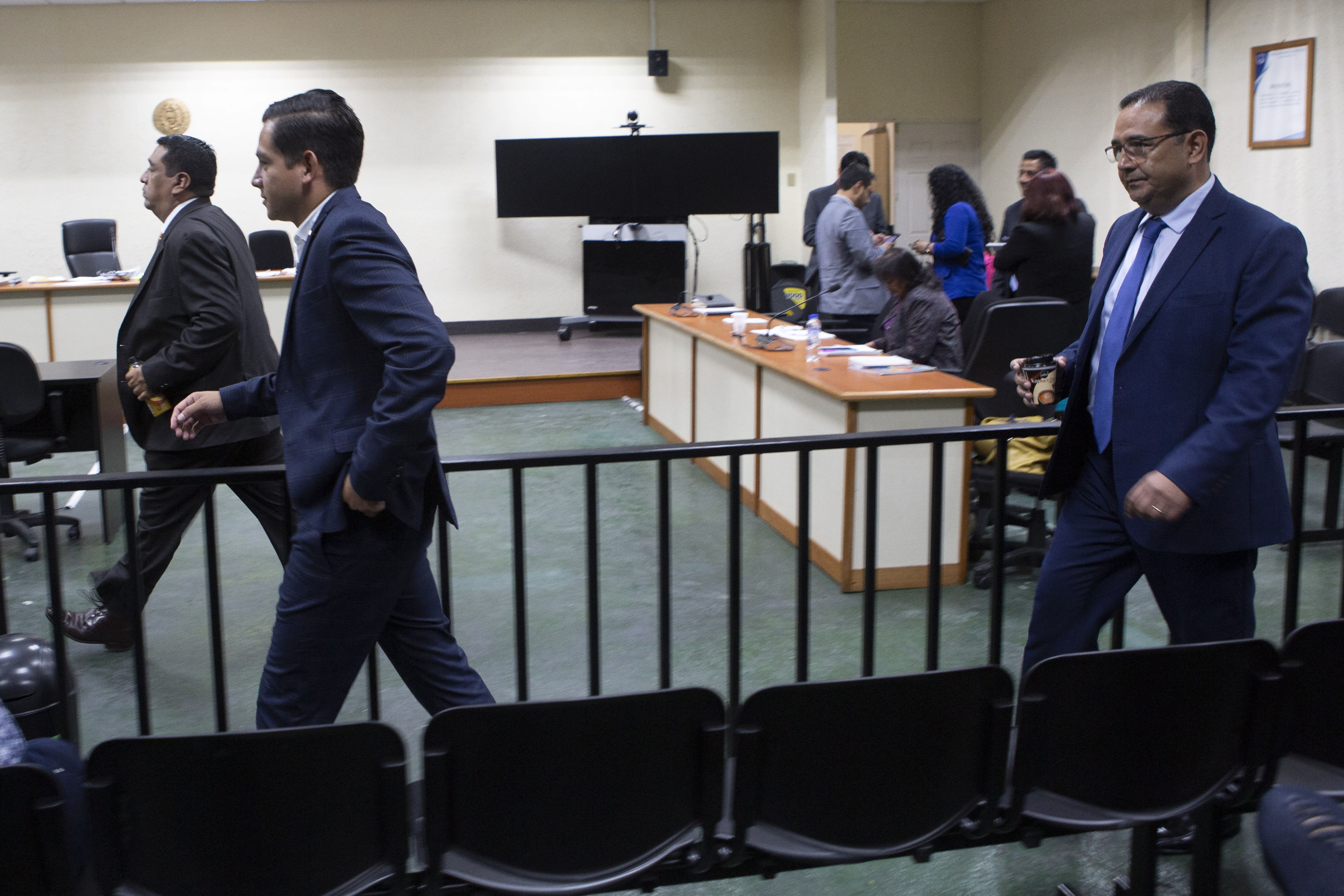 Jose Manuel Morales Marroquin, son of Guatemalan President Jimmy Morales, front left, and his uncle Samuel Everardo Morales, the president's brother, enters court in Guatemala City, Monday, Aug. 19, 2019. The court acquitted the pair who were singled out for a corruption case in 2013. (AP Photo/Moises Castillo)