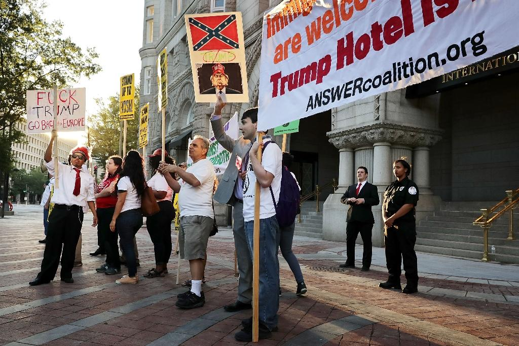 Demonstrators gather in front of the newly opened Trump International Hotel to protest against Republican presidential candidate Donald Trump and what they say are his racist, sexist and anti-immigration positions in Washington, DC (AFP Photo/Chip Somodevilla)