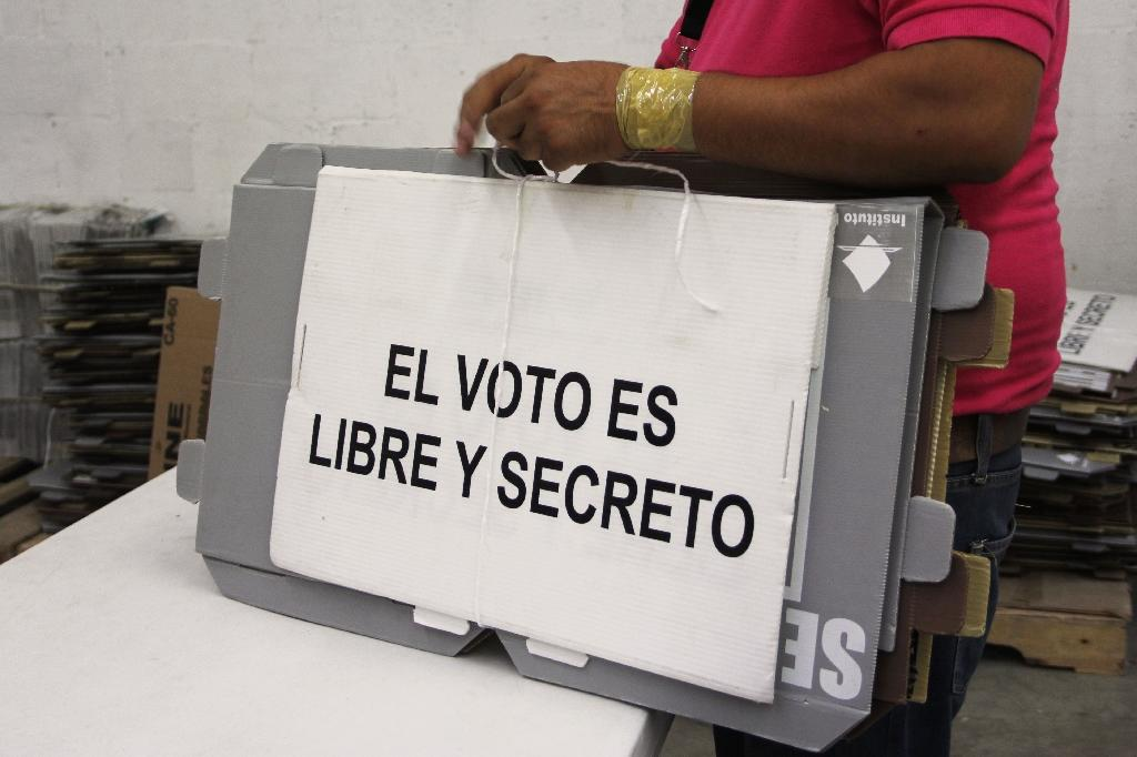 "Electoral workers prepare material, which reads ""the vote is free and secret,"" ahead of Mexico's presidential ballot (AFP Photo/Herika Martinez)"