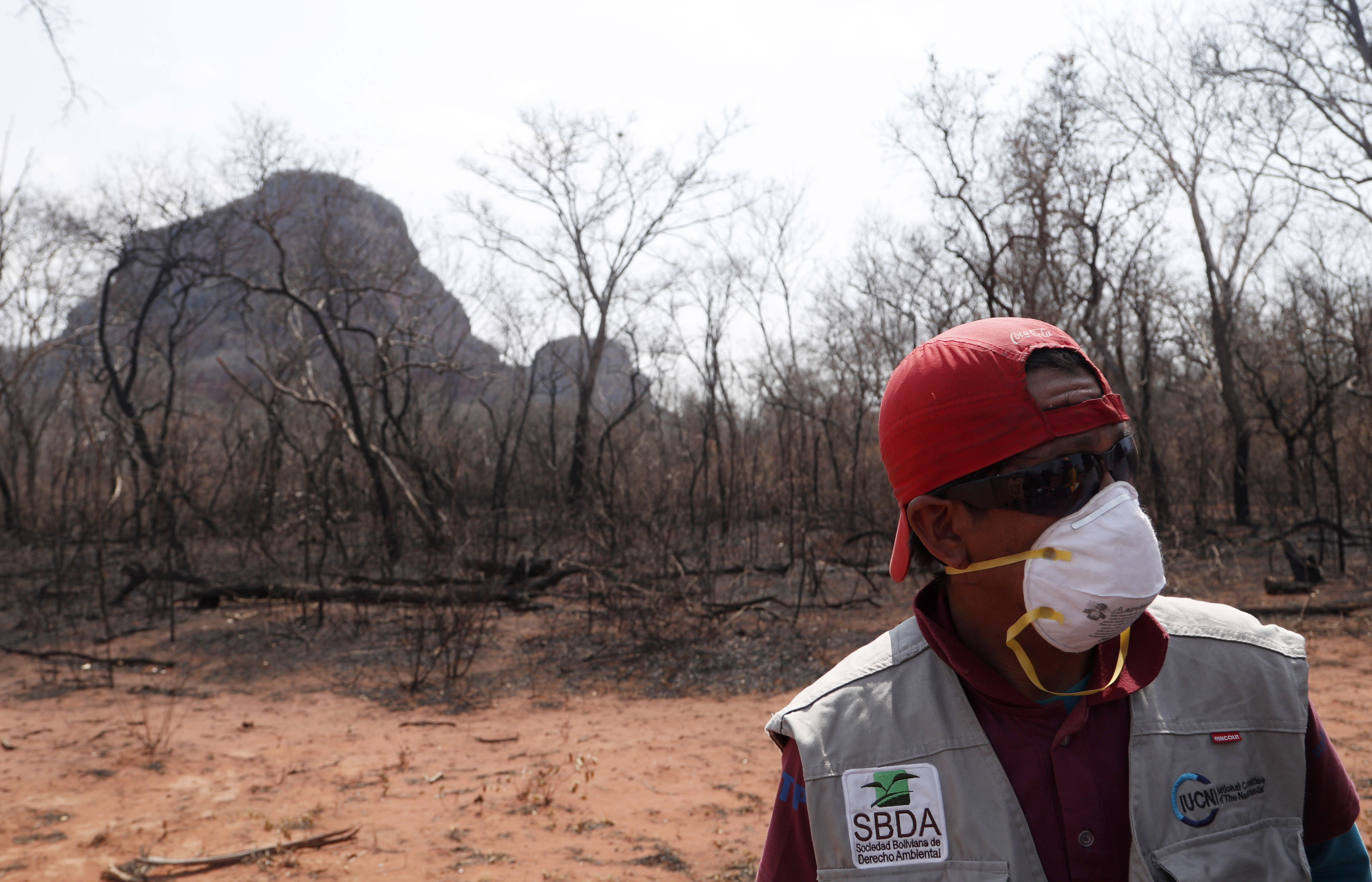 A volunteer stands on land scorched by wildfires in the Chiquitania Forest near Robore, Bolivia, Tuesday, Aug. 27, 2019. While global attention has been focused on fires burning across the Brazilian Amazon, neighboring Bolivia is battling its own vast blazes. (AP Photo/Juan Karita)