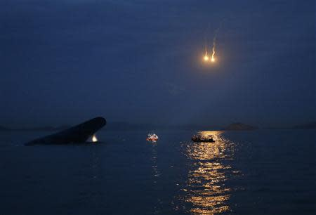 "South Korean ferry ""Sewol"" (L) is seen sinking at the sea off Jindo, as lighting flares are released for a night search, April 16, 2014. REUTERS/Kim Hong-Ji"