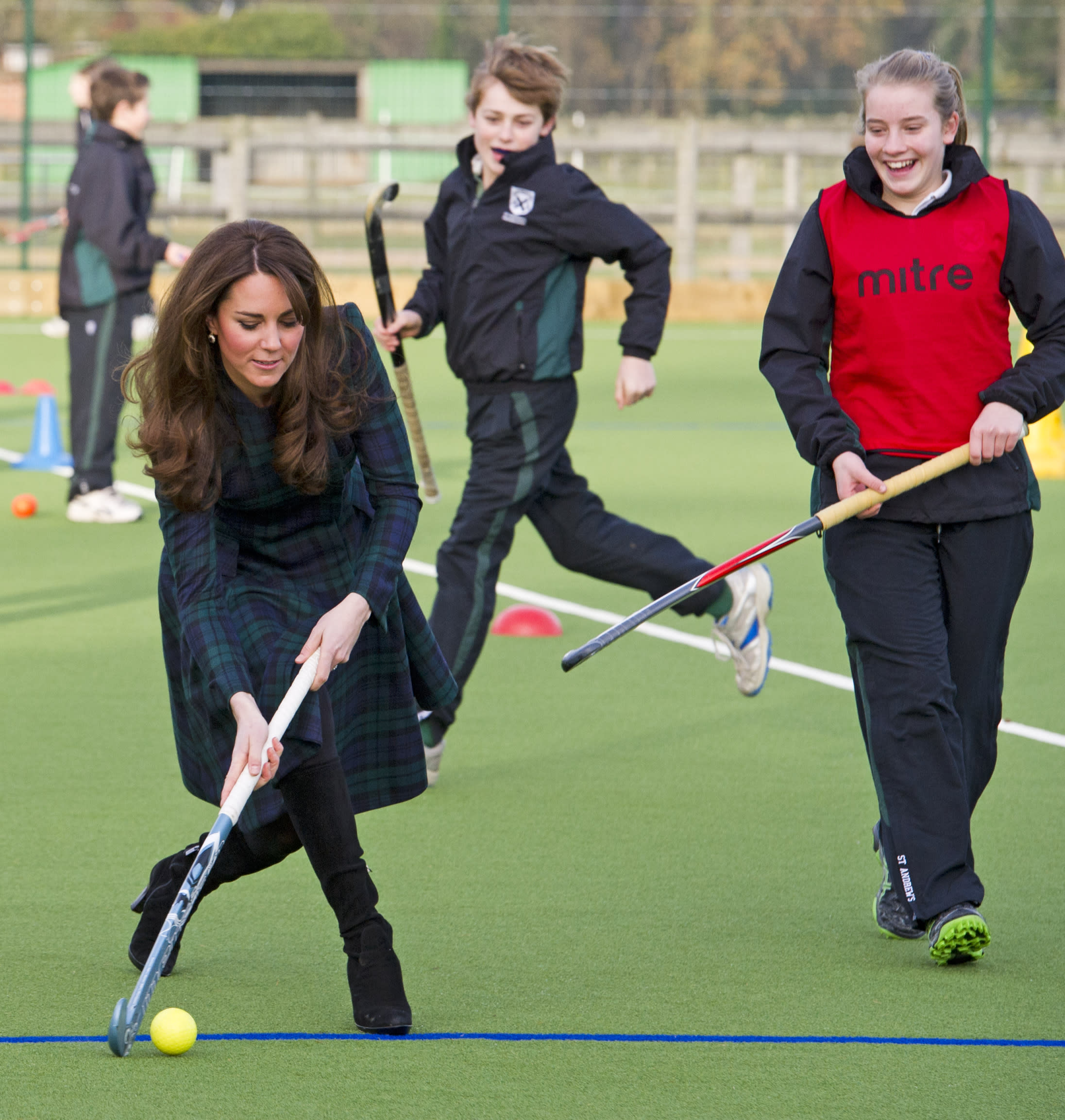 """Kate, the Duchess of Cambridge, left, plays hockey during her visit to St. Andrew's School, where she attended school from 1986 till 1995, in Pangbourne, England, Friday, Nov. 30, 2012. The Duchess of Cambridge has gone back to school. The royal, formerly known as Kate Middleton, played hockey and revealed her childhood nickname — Squeak — when she returned to her elementary school for a visit Friday. Kate told teachers and students at the private St. Andrew's School in southern England that her 10 years there were """"some of my happiest years."""" She said that she enjoyed it so much that she had told her mother she wanted to return as a teacher. (AP Photo/Arthur Edwards, Pool)"""