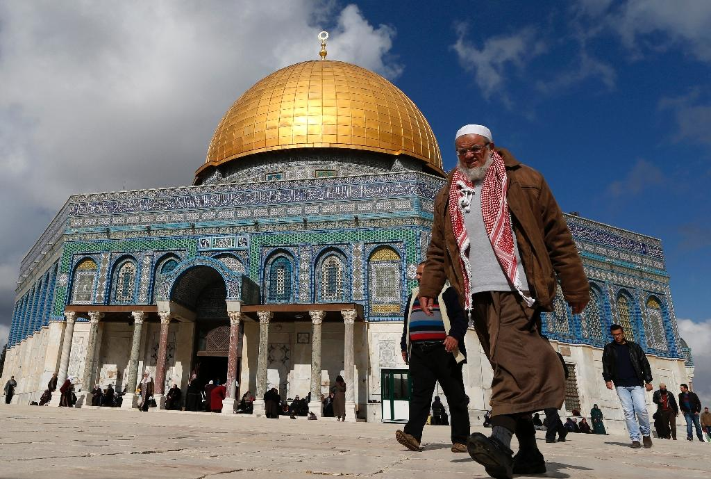 Palestinians walk past the Dome of Rock at the Al-Aqsa Mosque compound in Jerusalem's Old City, on January 13, 2017 (AFP Photo/Ahmad Gharabli)