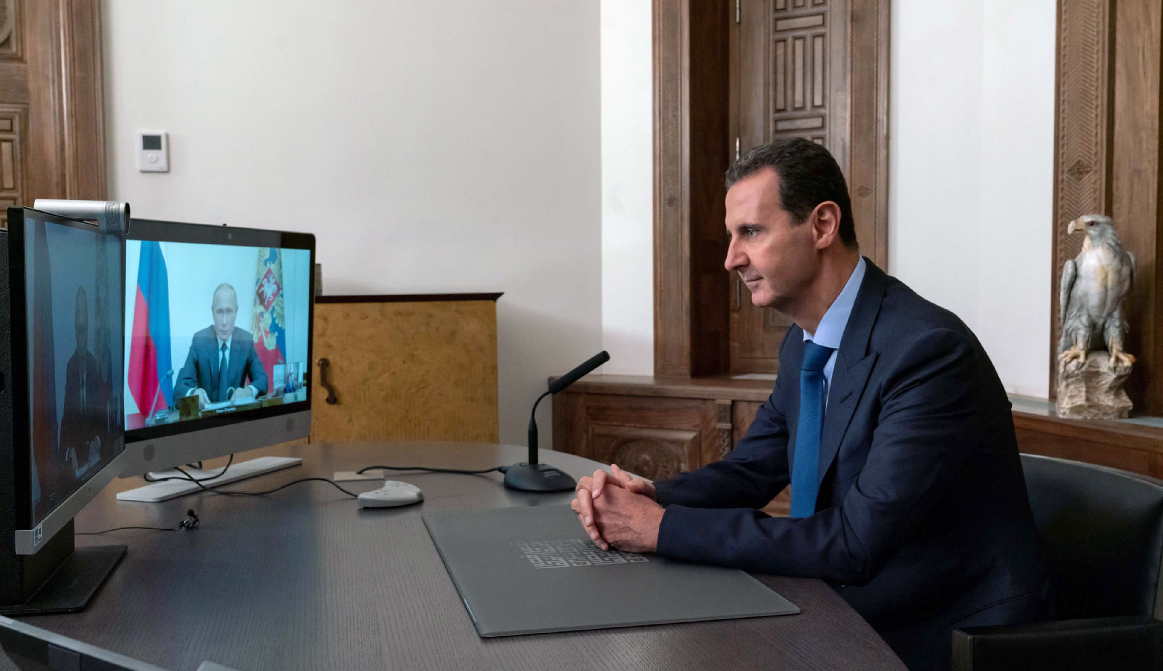 In this photo released by the Syrian official news agency SANA, Syrian President Bashar Assad listens to Russian President Vladimir Putin during their talks via video conference, in Damascus, Syria, Monday, Nov. 9, 2020. (SANA via AP)