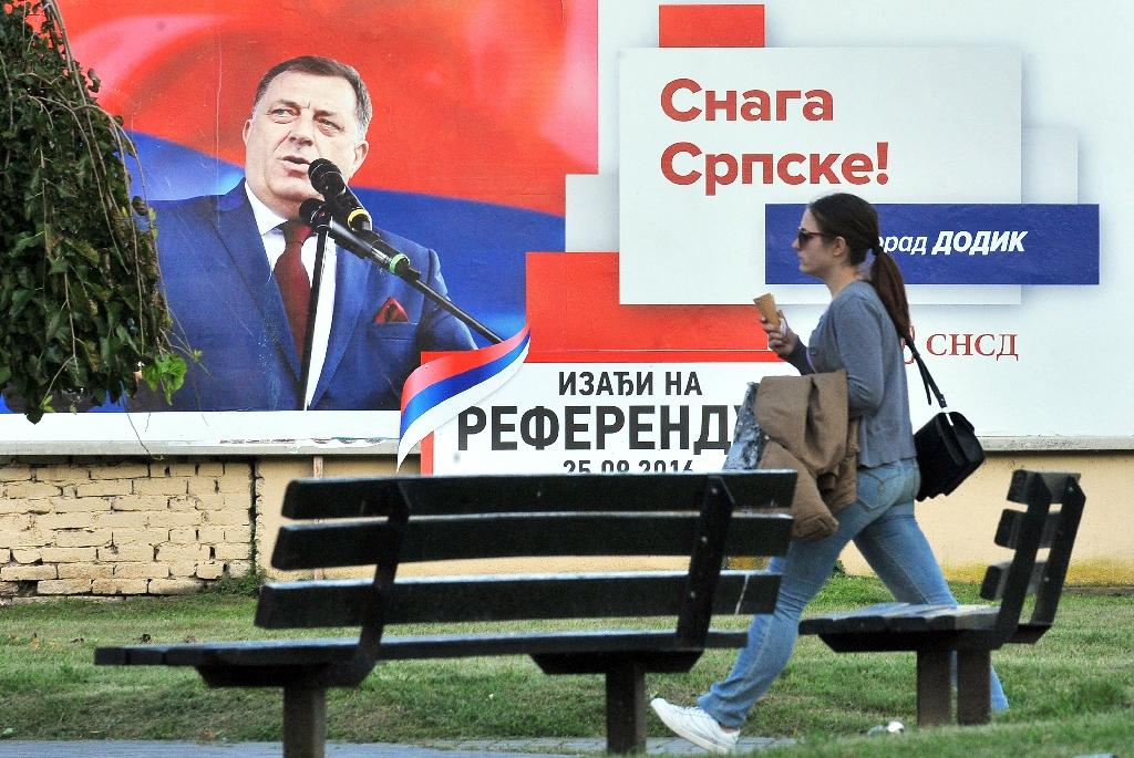 """A woman walks past a billboard featuring the leader of the Party of Independent Social Democrats Milorad Dodik reading """"Get out on Referendum Day 25.09.2016"""" (AFP Photo/Elvis Barukcic)"""