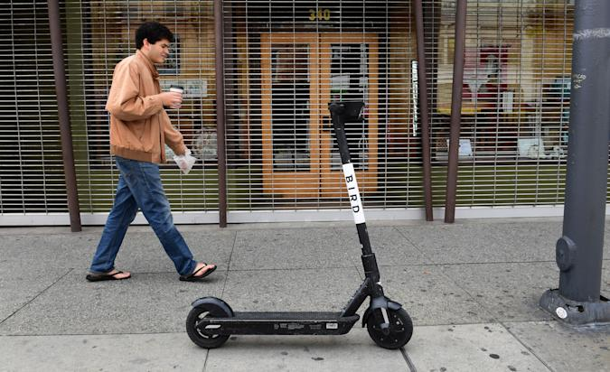 A man walks past a Bird scooter on a Los Angeles sidewalk on March 19, 2020. - Electric scooter companies Bird and Lime have suspended services across North America for an indefinite period amid the coronavirus epidemic and a drop in user numbers. (Photo by Frederic J. BROWN / AFP) (Photo by FREDERIC J. BROWN/AFP via Getty Images)