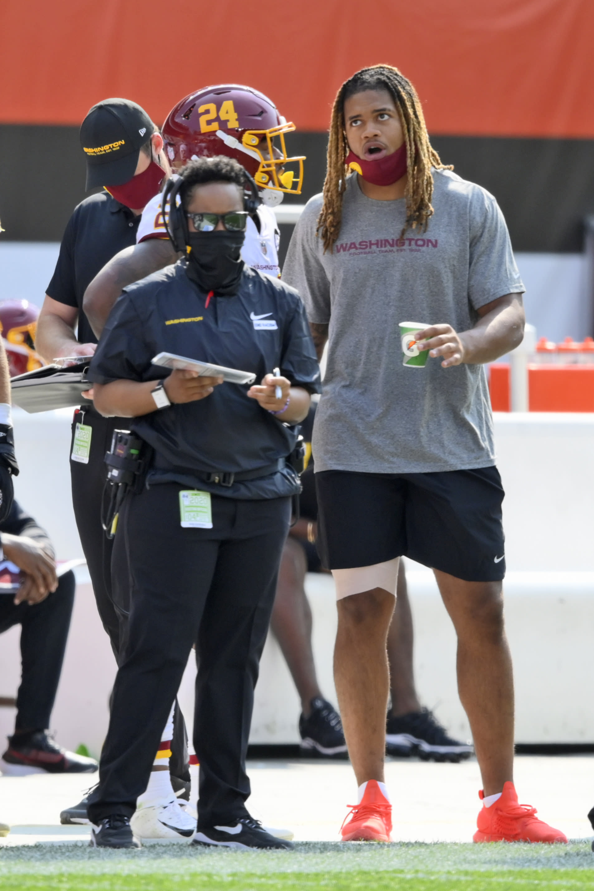 Washington Football Team defensive end Chase Young, right, watches form the sidelines during the second half of an NFL football game against the Cleveland Browns, Sunday, Sept. 27, 2020, in Cleveland. (AP Photo/David Richard)
