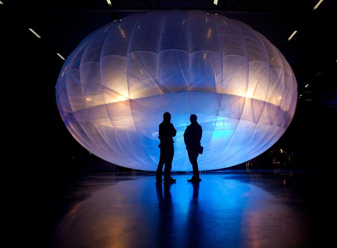 Visitors stand next to a high altitude WiFi internet hub, a Google Project Loon balloon, on display at the Airforce Museum in Christchurch on June 16, 2013. Google revealed top-secret plans on June 15 to send balloons to the edge of space with the lofty aim of bringing Internet to the two-thirds of the global population currently without web access.     AFP PHOTO / MARTY MELVILLE        (Photo credit should read Marty Melville/AFP via Getty Images)