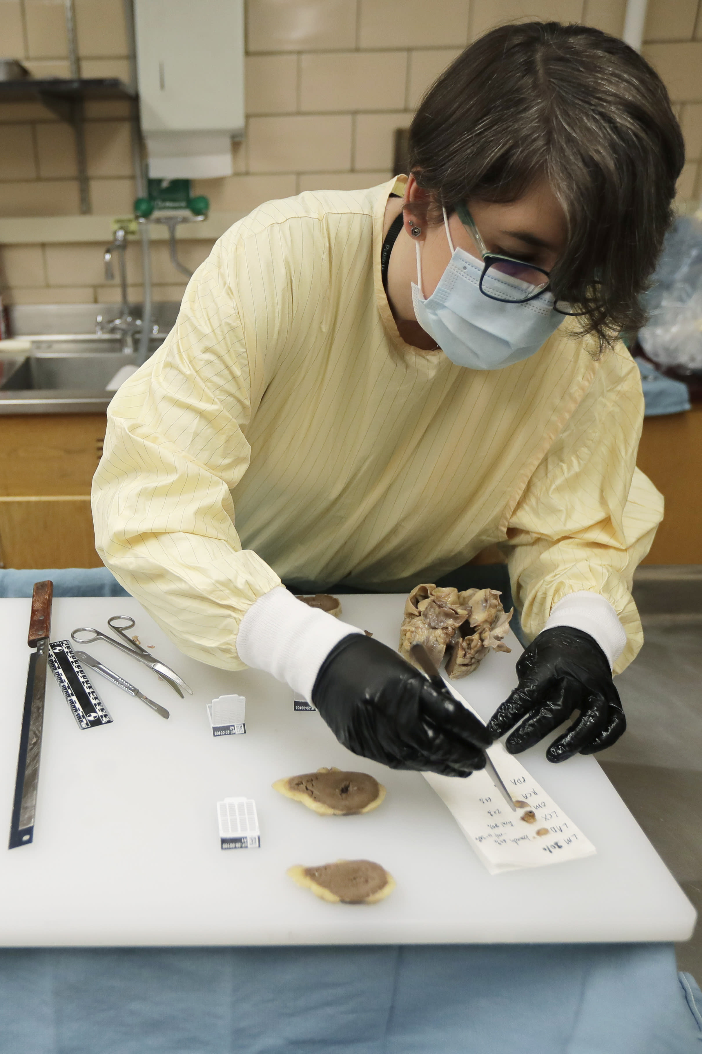 """Dr. Desiree Marshall, director of Autopsy and After Death Services for University of Washington Medicine, prepares samples from the preserved heart of a person who died of COVID-19 related complications, as she works in a negative-pressure laboratory, Tuesday, July 14, 2020, in Seattle. """"Each autopsy has the chance to tell us something new,"""" she says. And those insights from the bodies of the dead could lead to more effective treatment of the living. (AP Photo/Ted S. Warren)"""
