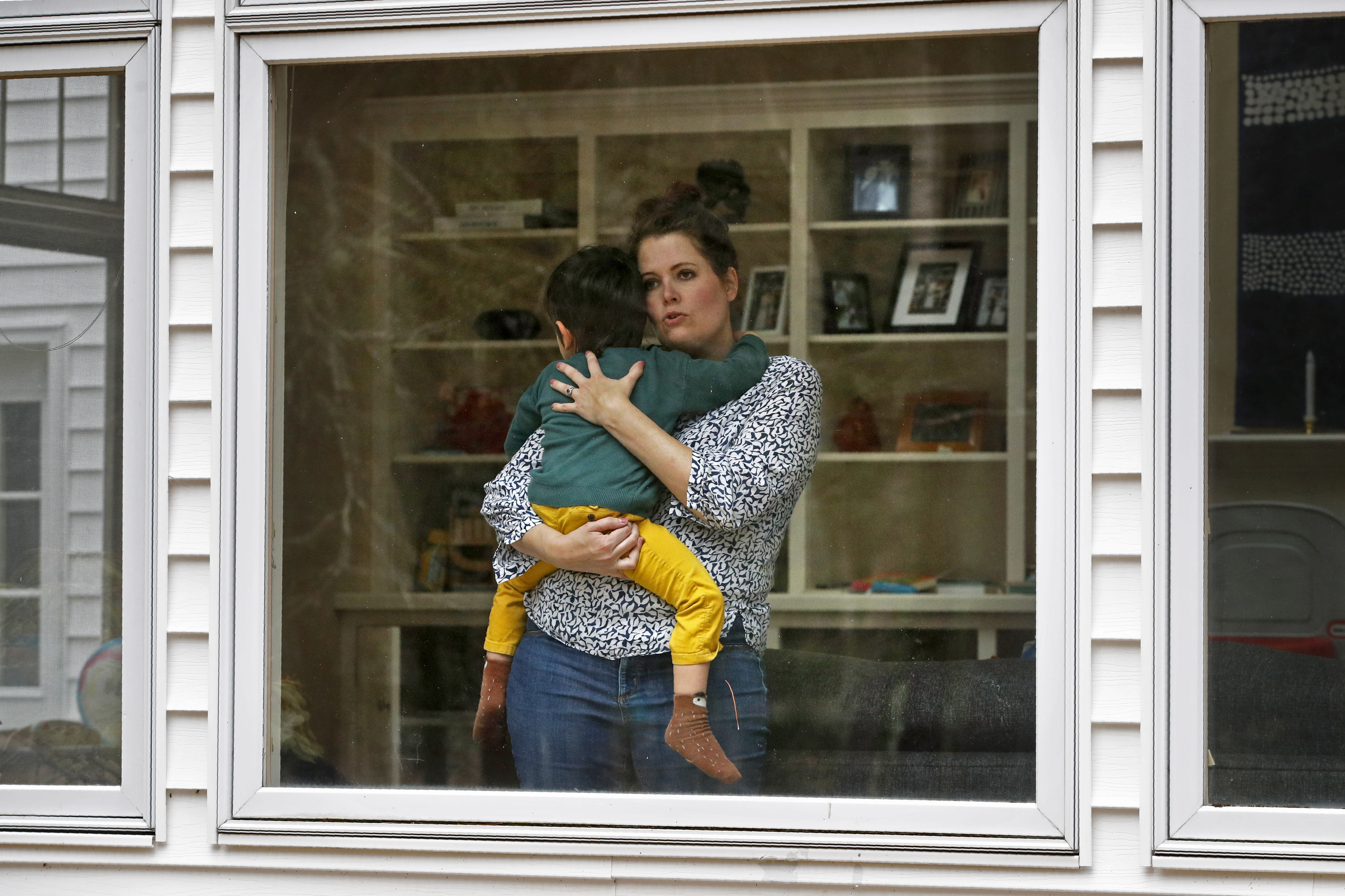 In this Wednesday, April 1, 2020 photo, Joy Engel holds her son at her home in Cape Elizabeth, Maine. Engel, who is pregnant, and her husband, Dr. Ben Hagopian, who works at a family practice and an urgent care clinic, decided to isolate themselves from each since the coronavirus outbreak. (AP Photo/Robert F. Bukaty)