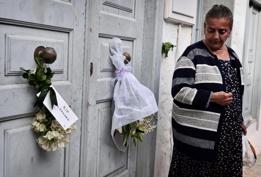 A former neighbour looks at flowers placed outside the summer house of late Canadian singer-songwriter and poet Leonard Cohen on the Greek island of Hydra, on November 12, 2016 (AFP Photo/Louisa Gouliamaki)