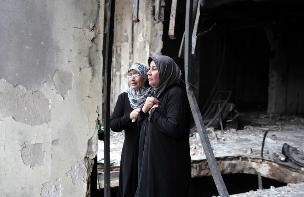 Iraqi women surveil the aftermath of a massive bombing in Baghdad's Karrada neighbourhood on July 4, 2016 (AFP Photo/Sabah Arar)