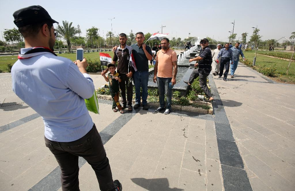 """Iraqis pose in the parade grounds outside parliament inside Baghdad's heavily fortified """"Green Zone"""" on May 1, 2016, the day after supporters of Shiite cleric Moqtada al-Sadr broke into the area after lawmakers failed to approve new ministers (AFP Photo/Ahmad Al-Rubaye)"""