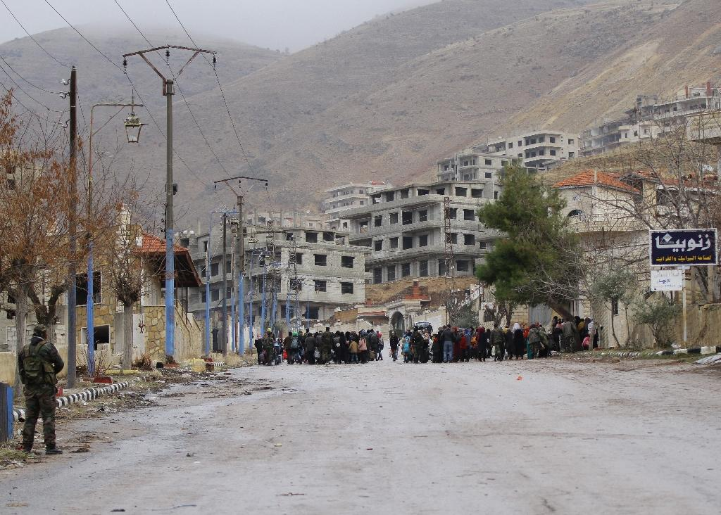 Residents of the besieged rebel-held Syrian town of Madaya wait for a convoy of aid from the Syrian Arab Red Crescent