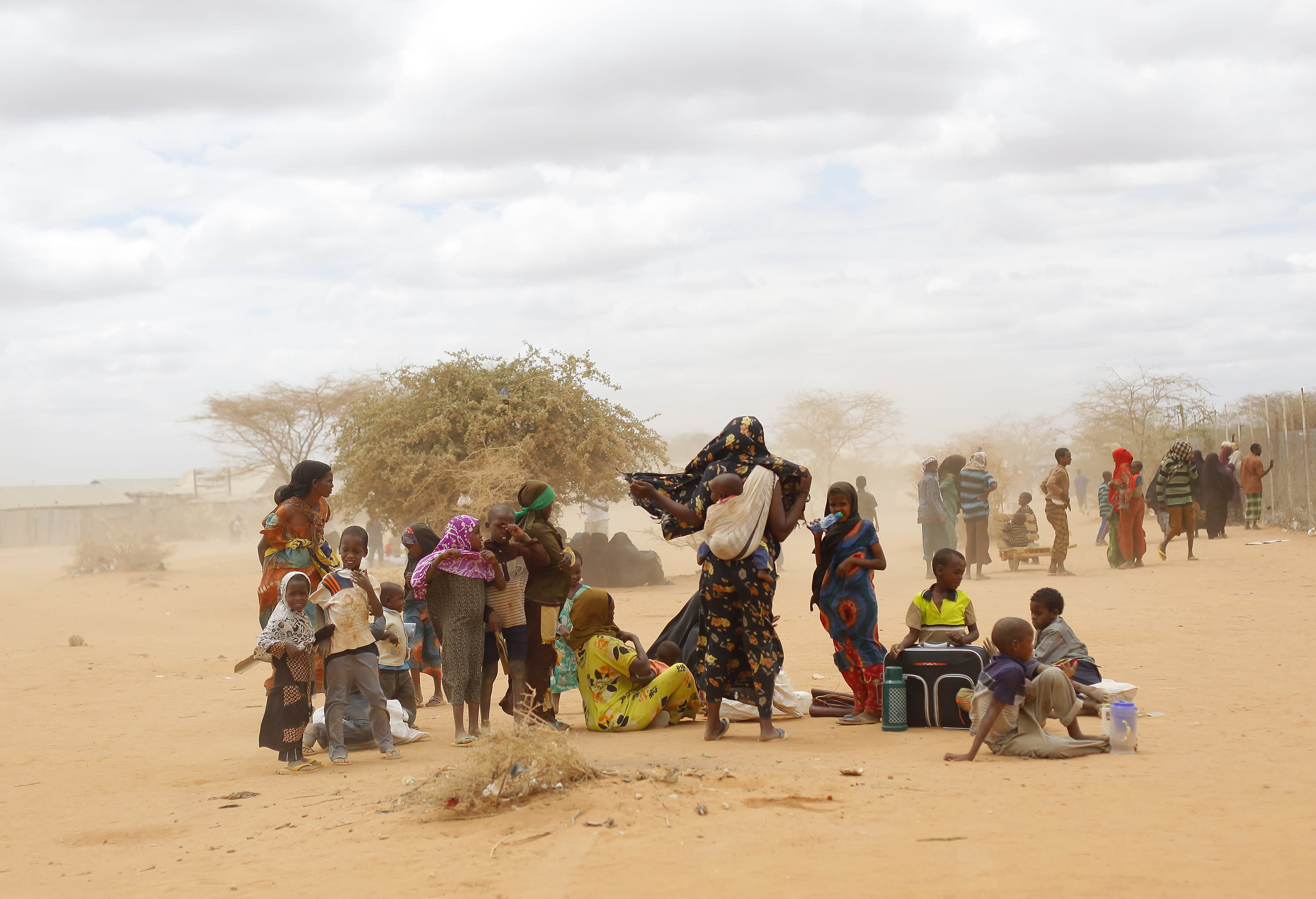FILE - In this Aug. 5, 2011 file photo, newly arrived Somali refugees wait outside a UNHCR processing center at the Ifo refugee camp outside Dadaab, eastern Kenya, 100 kilometers (62 miles) from the Somali border. Human-induced climate change contributed to low rain levels in East Africa in 2011, making global warming one of the causes of Somalia's famine and the tens of thousands of deaths that followed, a new study has found. (AP Photo/Jerome Delay, File)