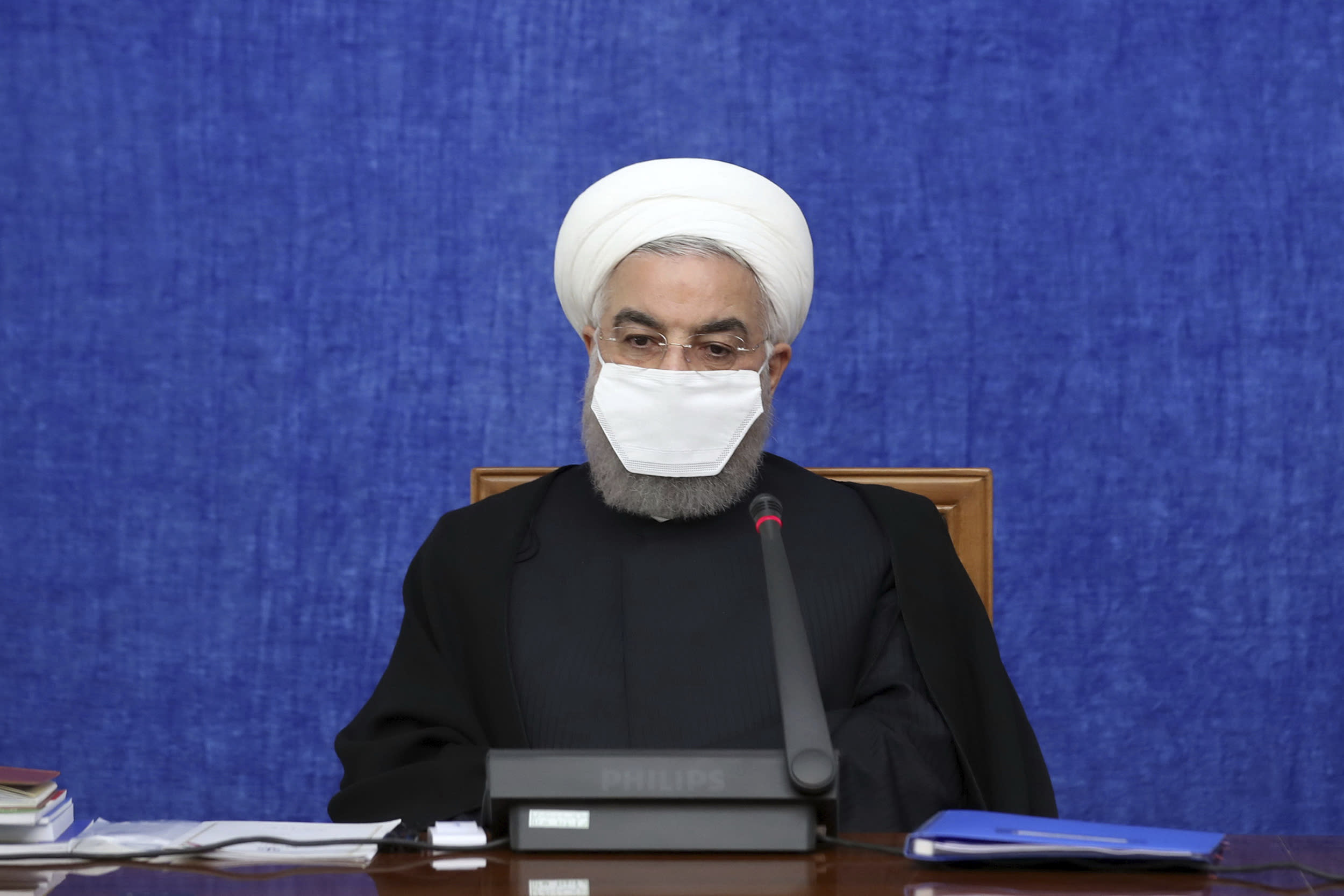 """In this Oct. 13, 2020, photo, released by the official website of the office of the Iranian Presidency, President Hassan Rouhani wearing a protective face mask to help prevent spread of the coronavirus attends a meeting in Tehran, Iran. Iran is confronting a new surge of infections that is filling hospitals and cemeteries alike. Weeks after Rouhani called in-person instruction at schools """"our first priority,"""" the government shut the newly resumed schools and universities in the capital. (Office of the Iranian Presidency via AP)"""